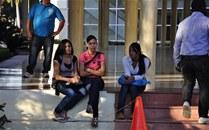 Estudiantes descansan en el aula Magna de la UAS D, mientras algunos miembros de la seguridad observan todo lo que ocurre en la zona mientras llegue el rector.