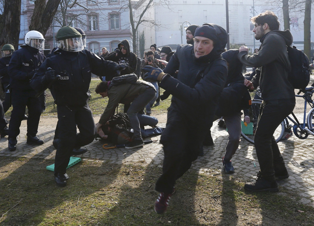 Anti-capitalist protesters scuffle with policemen near ECB building before the official opening of it's new headquarters in Frankfurt