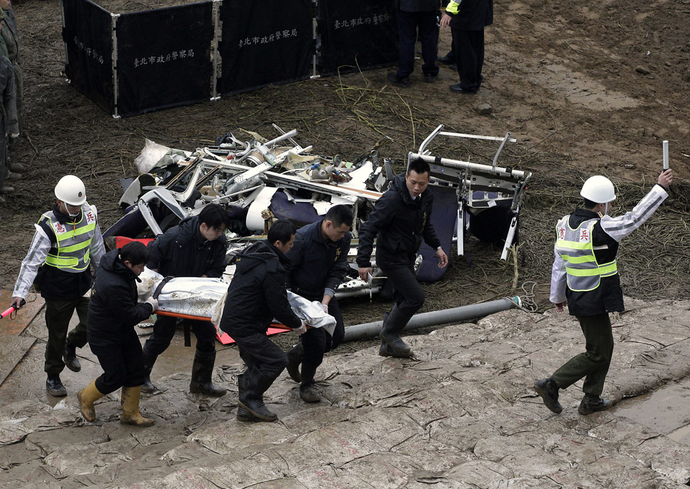 Emergency personnel carry a body of a passenger who died in the TransAsia Airways Flight GE235 plane crash in New Taipei City