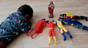 un niño rezando junto a sus superhéroes