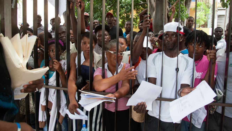 Migrantes, principalmente haitianos, exhiben sus documentos a funcionarios mientras esperan registrar su residencia legal en el ministerio del Interior en Santo Domingo, República Dominicana, el martes 16 de junio de 2015. El gobierno dominicano se prepara para comenzar esta semana a repatriar inmigrantes que no se hayan registrado en un programa especial para legalizar su estatus, mientras miles de personas hacen largas filas para tratar de inscribirse. (AP Photo/Tatiana Fernandez)